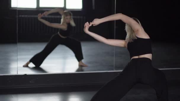 Flexibility of shoulders - training of dancer near mirror.