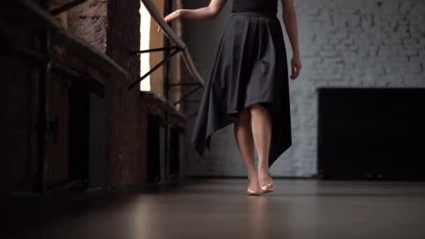 Girl in black dress walk in slow motion in dance studio.