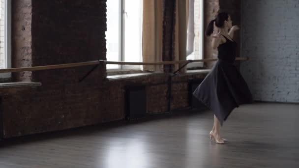 Grace lady in black dress makes turning in dance studio.