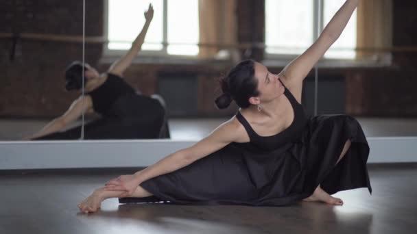 Girl in black dress makes stratching in dance studio near window.