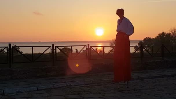 Člověk v ukrajinské krajině tancuje na kůtech na břehu při západu slunce ve dne