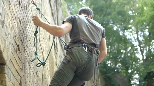 Young tourist climbing a sheer wall with long ropes in summer in slo-mo