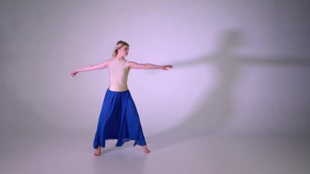Blondýnka dělá noha split a skákat na jedné noze v studio