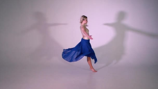 A yound blonde girl dancing ballet pirouette in slow motion