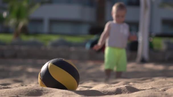 4k-malý chlapec se pohybuje v blízkosti valleyballu na pláži.