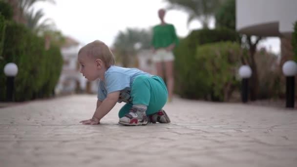 das Baby sitzt auf dem Bürgersteig und schaut unter den Busch - lustige Aktion.