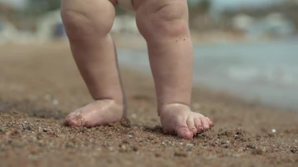 Hezké malé nohy malého dítěte stojí na písku na pláži.