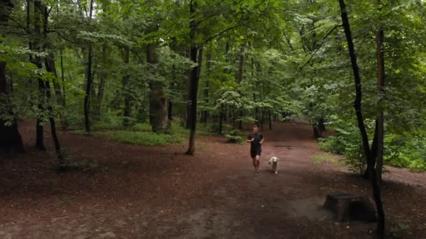 Young strong man in a Tshirt and shorts running with a dog in a forest