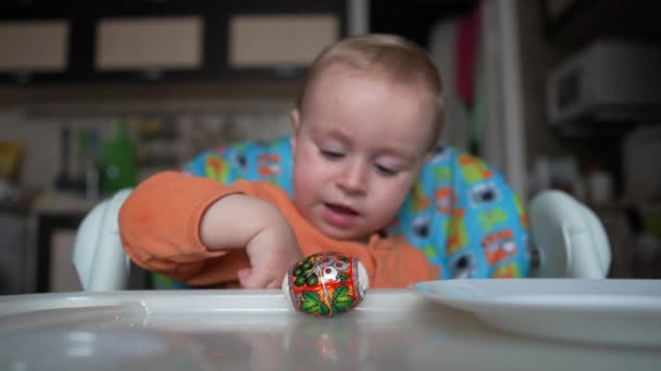 One year old boy sits and play with easter eggs in slow motion.
