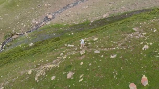 4k - The guy quickly goes up the mountain, aerial action with drone
