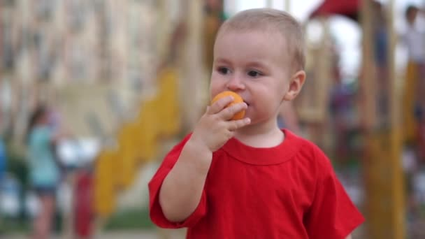 A small boy trying to bite off a toy tangerine and throws it away in slow motion