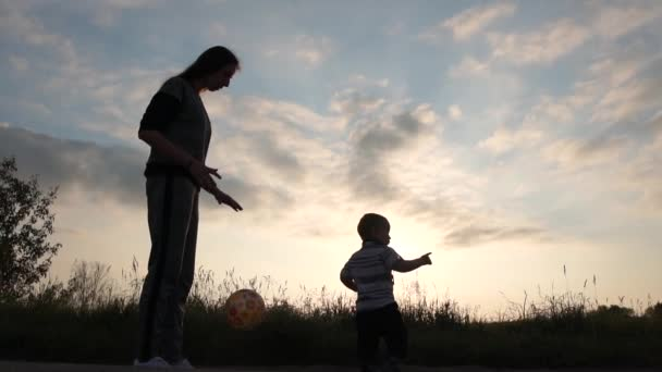 Mom fills the ball on the ground like in basketball near a baby, slow motion