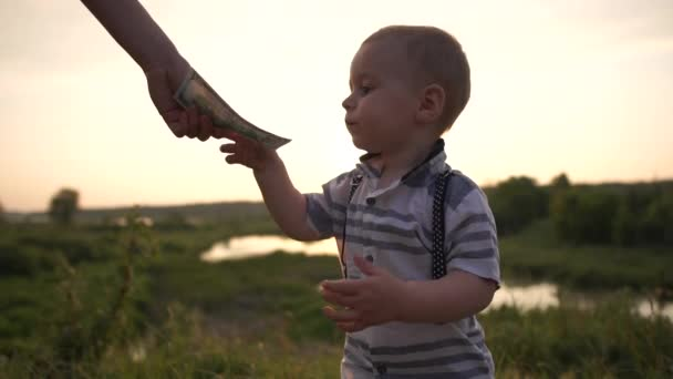 A cute small boy was given one hundred dollar bill on nature in slow motion