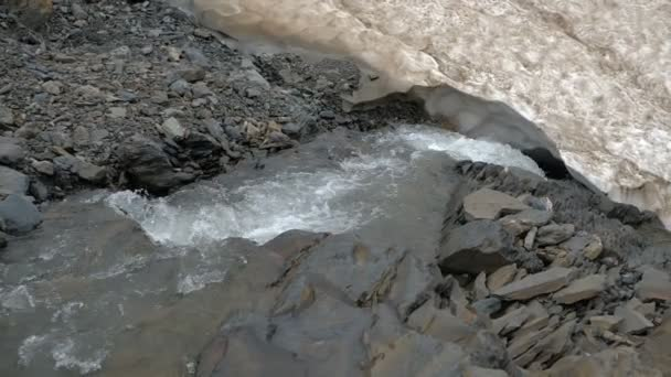 Burácející horská řeka, která v létě protéká mezi ledem v Gruzii