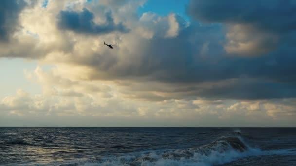 A viharos Fekete-tenger egy repülő helikopter a naplementében nyáron slo-Mo