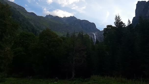 Narrow waterfall and a dark forest before it in Georgia in summer in slo-mo