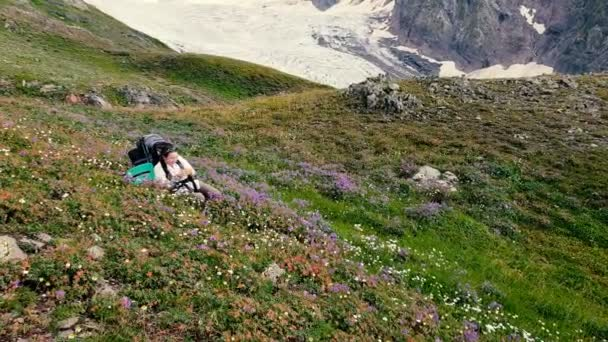 Female mountaineer sitting and smiling among flowers on a mountain in slo-mo