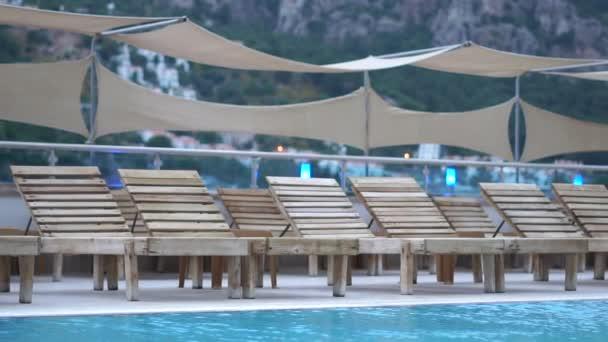 kostenlose Liegestühle am Pool inmitten der Berge in Zeitlupe