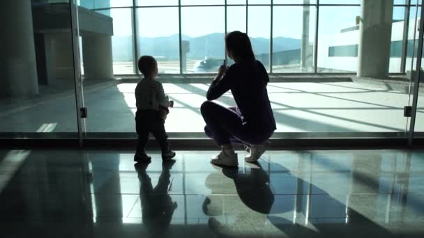 Mom and small son look at the planes through the large windows at the airport