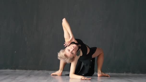 Attractive girl doing bridge and rolling her legs while dancing on the floor in a studio in slo-mo