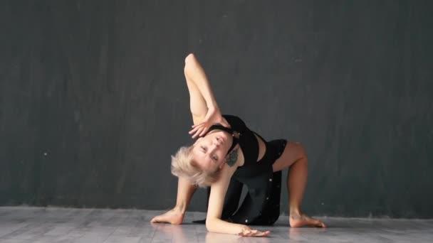 Atraktivní dívka při tancování na podlaze v ateliéru ve studiu v slo-mo