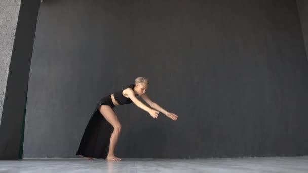 schlankes blondes Mädchen beim Wagenrad, während es im Studio in Slo-mo künstlerisch tanzt