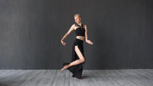 anmutiges blondes Mädchen, das im Studio im Slo-mo seine Hände schwenkt