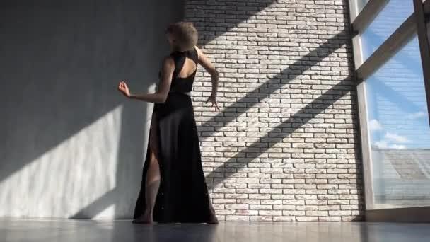 Incredible blonde girl dancing contemporary at a brick wall in studio in slo-mo