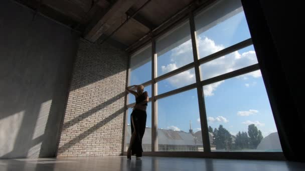 Romantic blonde girl dancing contemporary at a window at sunset in studio in slo-mo