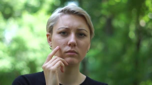 La donna bionda irritata cerca di calmarsi accarezzando il collo nel parco in slo-mo