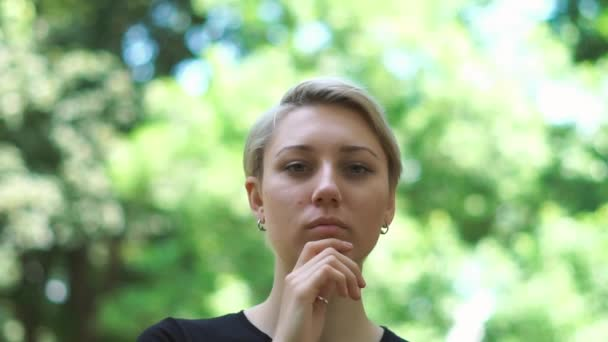 Beautiful blond woman looking and estimating somebody in a park in summer in slo-mo