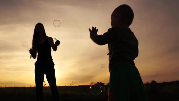 Beautiful mother standing and playing with soap bubbles and her kid at sunset in slo-mo