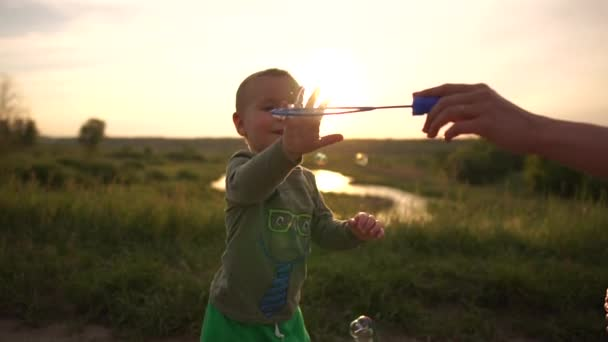 Cheery mum running and playing with soap bubbles and her kid at sunset in slo-mo