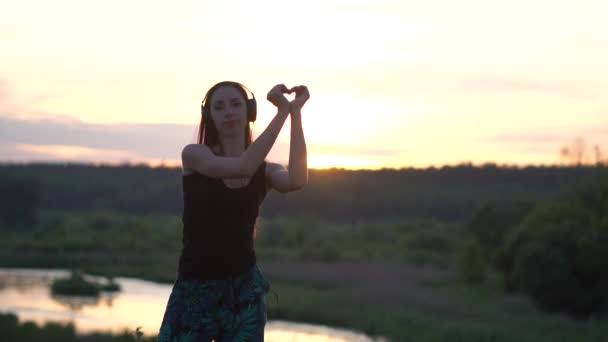 Happy girl dancing and showing a heart gesture at nice lake at sunset in slo-mo