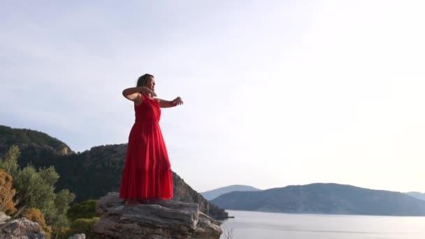 Egy nő kezet emel az oldalukon, lassú mozgásban élvezi a hegyre néző kilátást