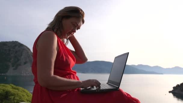 Unavená žena pracující v laptopu a markýze sedící na mořské krajině
