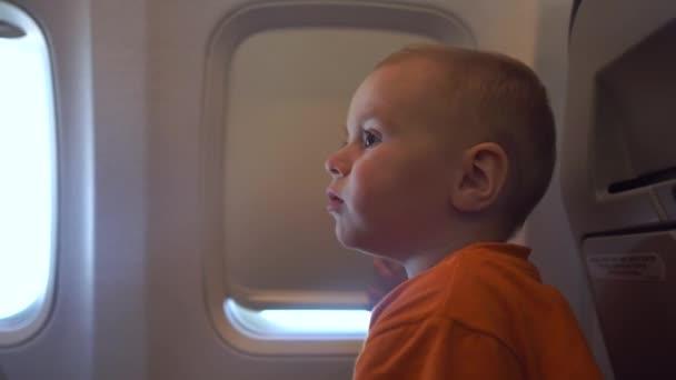 4k - Das Baby versucht, das Vorhangfenster im Flugzeug zu öffnen