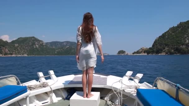 Young pretty girl dancing on the bow of a boat in slow motion
