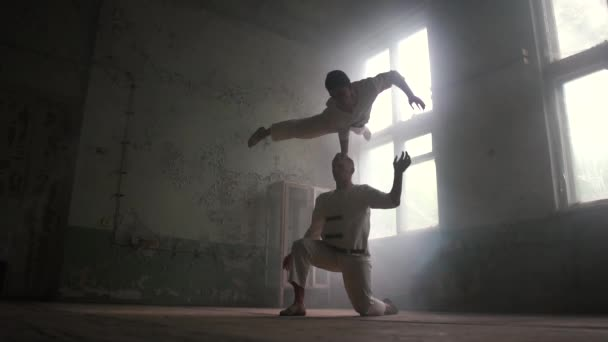 One kook man standing and the second doing crocodile asana in hall in slo-mo