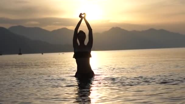 Girl made a heart from her hands above her head while in the sea in slow motion