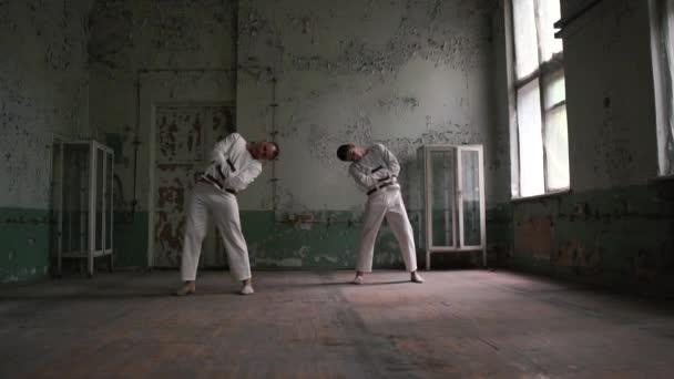 Két elmebeteg férfiak álló és hajlító egymásnak kopott szobában slo-Mo