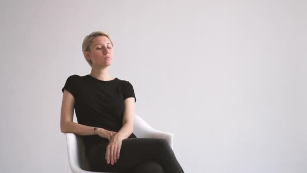 Stylish young blonde woman sitting and meditating in a white studio in slo-mo
