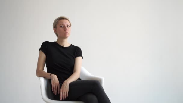 Chic young blonde woman sitting elegantly in a white studio in slo-mo