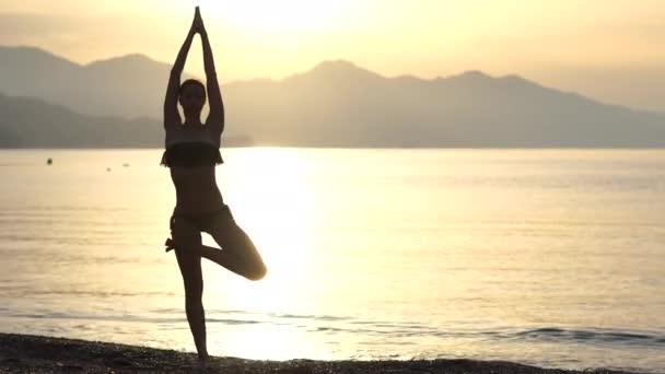 4k-půvabná dívka, která při východu slunce dělá na pobřeží jóby, pomalý pohyb