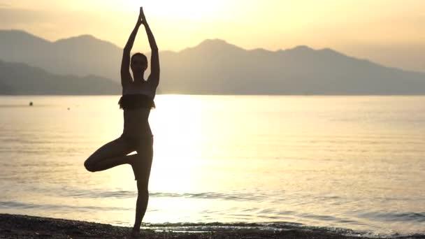 4k-nő Silhouette csinál jóga Asana a tengerparton napkelte, lassított