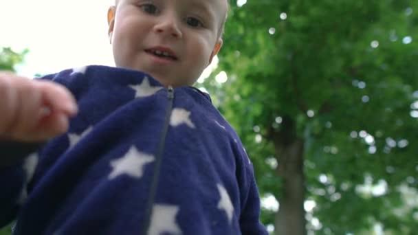 fröhliches blondes Kind, das im Sommer im Slo-mo auf einer Wiese nach unten schaut und lächelt