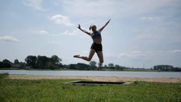 aktive fröhliche blonde Mädchen springen auf einem Trampolin in der Natur in Zeitlupe