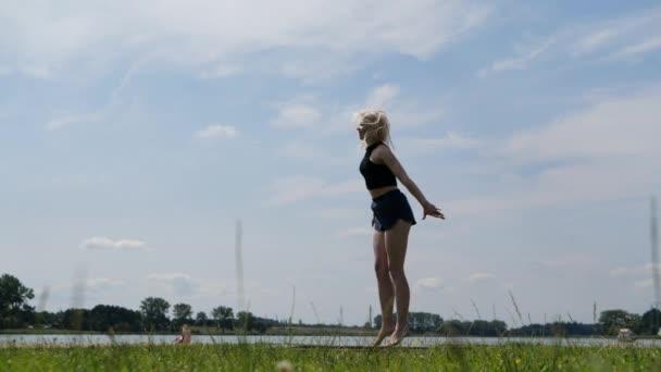 junges Mädchen, das auf einem Trampolin springt und in der Luft Bindfäden dreht, Zeitlupe