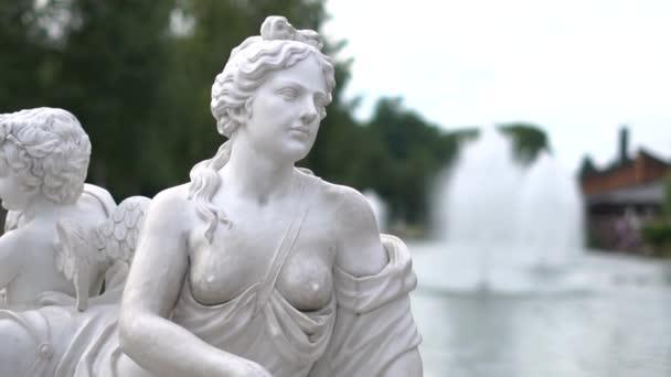 Egy meztelen nő szobra egy tó hátterében egy parkban lassított felvételen