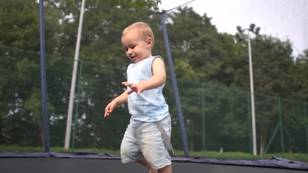 Lächelndes blondes Kind springt in Zeitlupe auf ein Trampolin